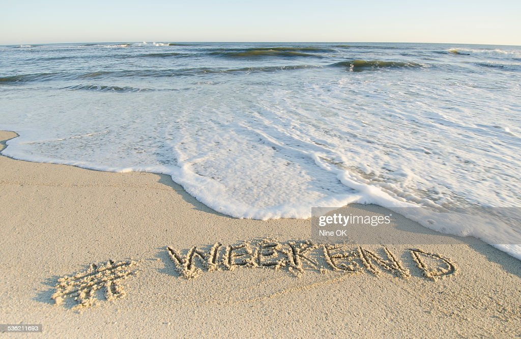 "Hashtag ""Weekend"" written in sand on beach : Stock Photo"