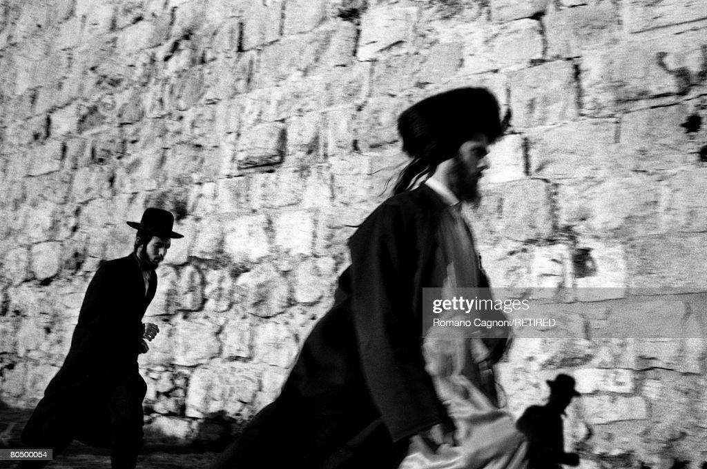 A Hasidic (right) and an Orthodox Jewish man hurry along beside a city wall, Jerusalem, circa 1990.