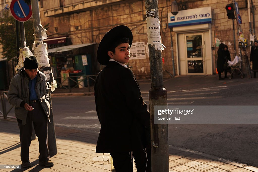 A Hasidic boy pauses in an Orthodox neighborhood on November 30, 2014 in Jerusalem, Israel. Nine Israelis have been killed in a series of stabbings, shootings and hit-and-run attacks in Jerusalem over the past month, unsettling the ancient city of Jerusalem where Jews, Christians and Muslims have lived side by side for thousands of years. The tension and violence on the streets of the city is threatening to further isolate communities and encourage extremist politicians to exploit the situation.