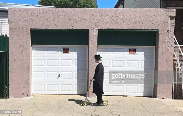 hasidic jew man on a scooter - hasidic jews stock photos and pictures