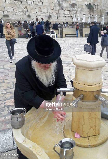 hasidic jew washing his hands before praying at the holy western wall. - jewish prayer shawl stock pictures, royalty-free photos & images