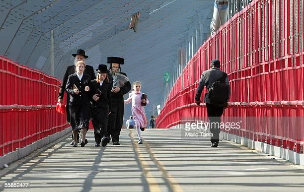 Hasidic Jews walk across the Williamsburg Bridge on their way to perform a traditional Tashlich ceremony October 4 2005 in the Brooklyn borough of...