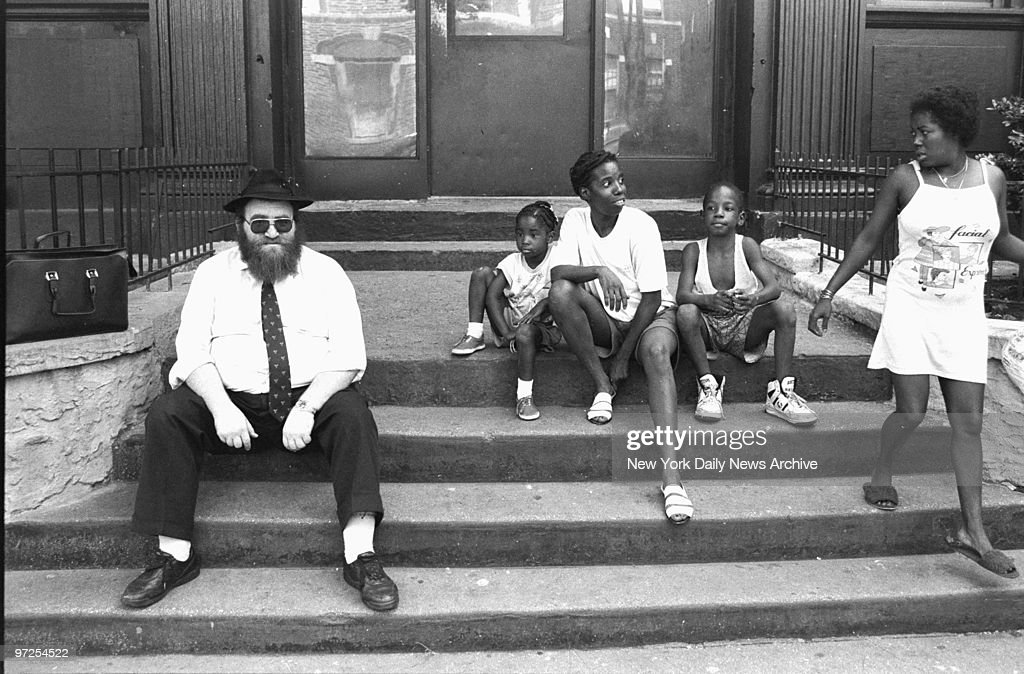 Hasidic man and black children share a stoop in Crown Heights where rioting erupted after two black 7-year-olds, Gavin and Angela Cato, were hit by a car driven by a member of the Hasidic Jewish community. Gavin died. Hours later, Yankel Rosenbaum. a young Hasidic scholar, was attacked by a mob and fatally stabbed by Lemrick Nelson, a 16-year-old black.Street violence continued for days with confrontations between blacks and Hasidim.
