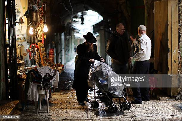 Hasidic man walks by a Muslim merchant in the Old City in Jerusalem on November 26 2014 in Jerusalem Israel Nine Israelis have been killed in a...