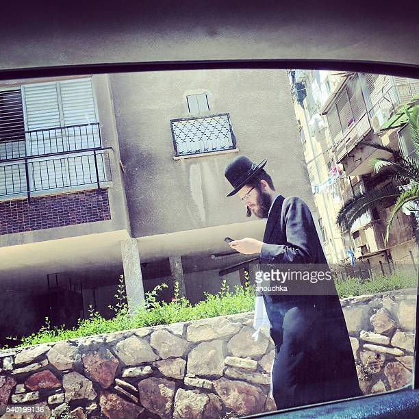 hasidic man with mobile phone on bnei brak street, israel - haredi judaism stock photos and pictures