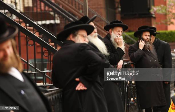 Hasidic men pause in a Jewish Orthodox neighborhood in Brooklyn on April 24 2017 in New York City According to a new report released by the...