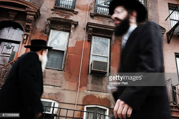 Hasidic men walk through a Jewish Orthodox neighborhood in Brooklyn on April 24 2017 in New York City According to a new report released by the...