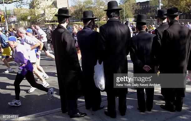 Hasidic men watch as runners in the 1999 New York City Marathon wind their way through Williamsburg Brooklyn