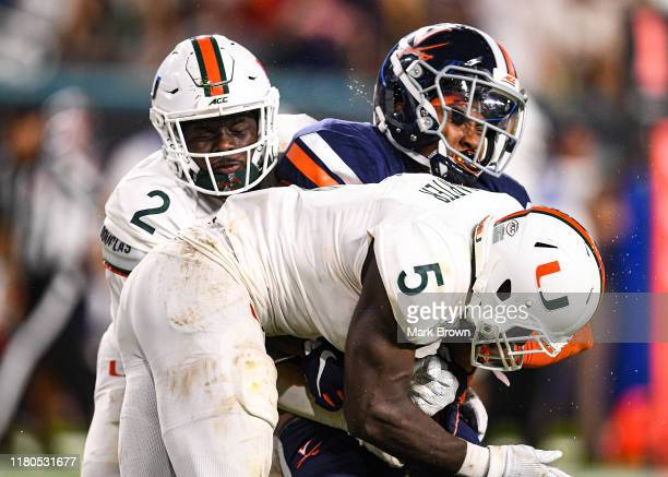 Hasise Dubois of the Virginia Cavaliers is hit by Amari Carter of the Miami Hurricanes while trying to catch a pass in the second half at Hard Rock...