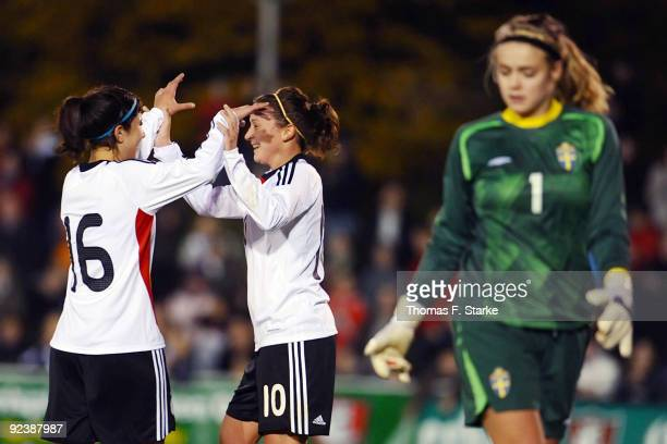 Hasret Kayicki and Ramona Petzelberger of Germany celebrate their teams first goal while Hilda Carlen of Sweden looks dejected during the women's...