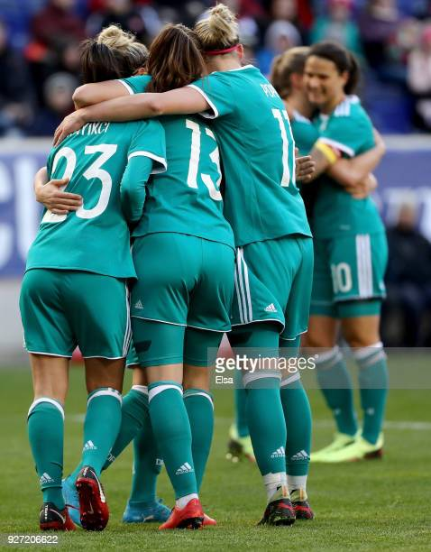 Hasret Kayikci of Germany is congratulated by teammates Sara Däbritz and Alexandra Popp after she scored in the first half against England during the...