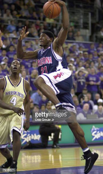 Hassan Adams of the Arizona Wildcats shoots against Hakeem Rollins of the Washington Huskies on January 29 2004 at Edmundson Pavilion in Seattle...
