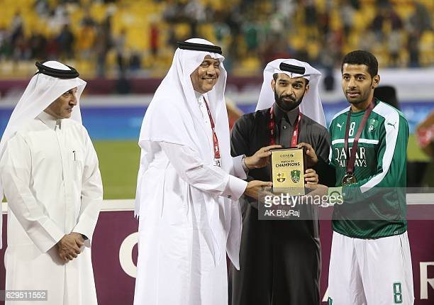 Hassan Al Thawadi Secretary General, Supreme Committee for Delivery & Legacy presenting a memento to Taisir al Jassim, caption of Al-Ahli Saudi FC...