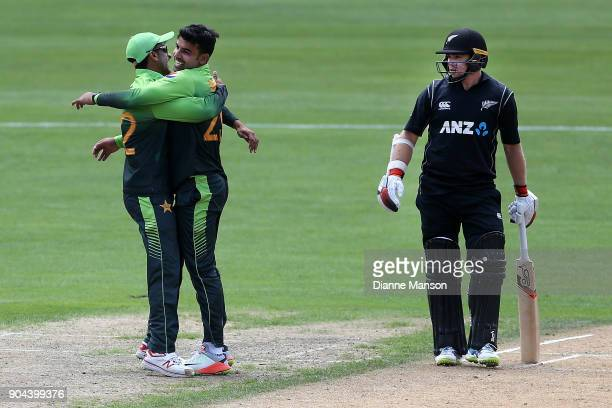 Hassan Ali and Shadab Khan of Pakistan celebrate the dismissal of Henry Nicholls of New Zealand as teammate Tom Latham looks on during the third game...