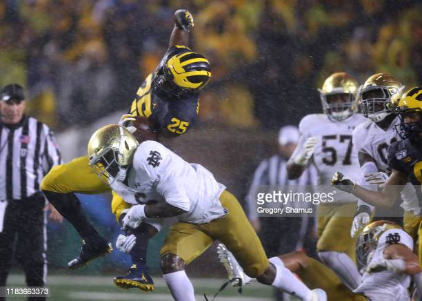 Hassan Haskins of the Michigan Wolverines tries to jump over the tackle of Jeremiah OwusuKoramoah of the Notre Dame Fighting Irish during a first...