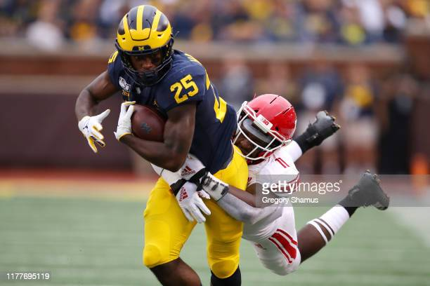 Hassan Haskins of the Michigan Wolverines tries to shake the tackle of Drew Singleton of the Rutgers Scarlet Knights during a first quarter run at...