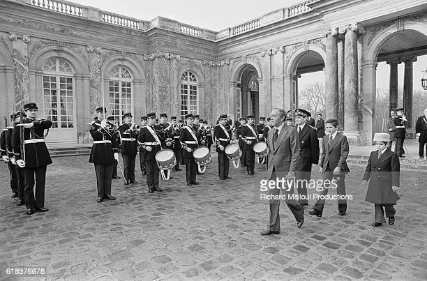 Hassan II King of Morocco is welcomed by a military band at an event in Paris France Joining him are his sons Crown Prince Sidi Mohammed and Prince...