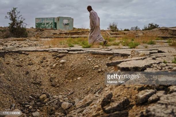Hassan Kanazri, a 63-year-old tomato farmer, walks through the former grounds for the Numeira Salt company and where sinkholes have appeared, ground...