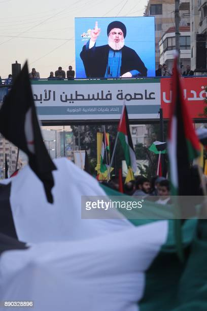 Hassan Nasrallah the head of Lebanon's militant Shiite movement Hezbollah addresses the crowds through a giant screen at a rally agains US President...