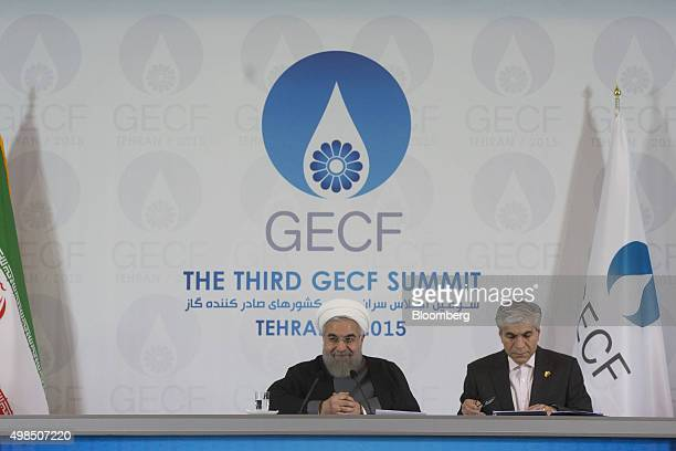 Hassan Rouhani Iran's president left reacts while Mohammad Hossein Adeli secretary general of the Gas Exporting Countries Forum reads notes during a...