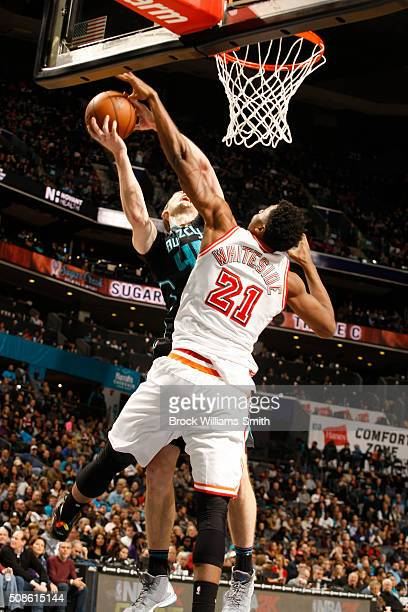 Hassan Whiteside of the Miami Heat attempts the block against Cody Zeller of the Charlotte Hornets during the game at the Time Warner Cable Arena on...