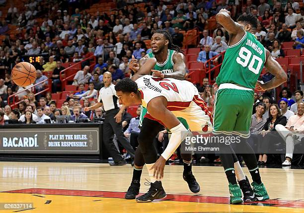 Hassan Whiteside of the Miami Heat fights for a loose ball with Amir Johnson and Jae Crowder of the Boston Celtics during a game at American Airlines...