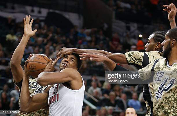 Hassan Whiteside of the Miami Heat has his shot blocked by Kawhi Leonard of the San Antonio Spurs at ATT Center on March 23 2016 in San Antonio Texas...