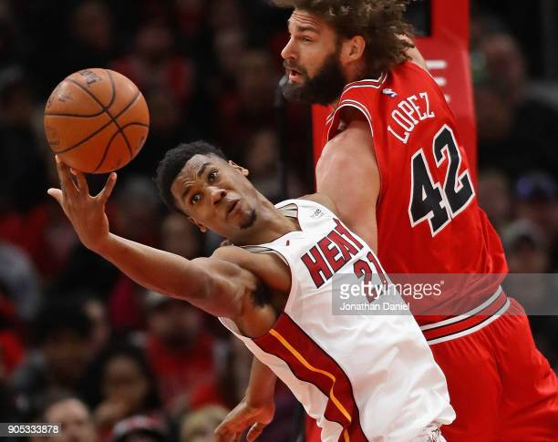 Hassan Whiteside of the Miami Heat reaches for a rebound next to Robin Lopez of the Chicago Bulls at the United Center on January 15 2018 in Chicago...