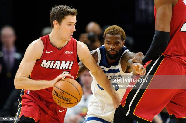 Hassan Whiteside of the Miami Heat sets a pick for Aaron Brooks of the Minnesota Timberwolves as teammate Goran Dragic drives to the basket during...