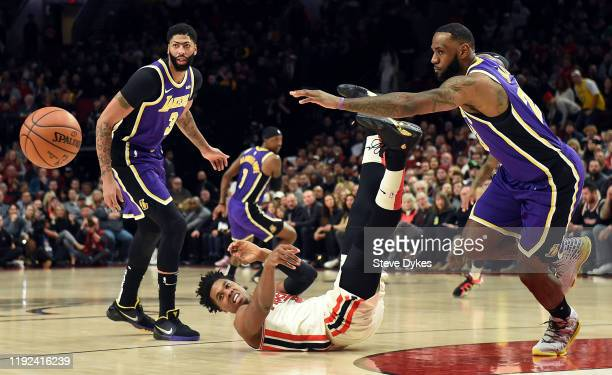 Hassan Whiteside of the Portland Trail Blazers is knocked to the floor as Anthony Davis and LeBron James of the Los Angeles Lakers go after the ball...
