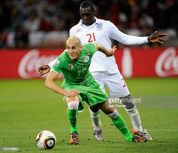 Hassan Yebda of Algeria watched by Emile Heskey of England during the 2010 FIFA World Cup South Africa Group C match between England and Algeria at...