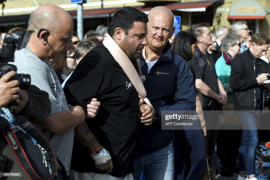 Hassan Zubier (2ndL), injured in a mass stabbing as he attempted to help a stabbing victim, is pictured at the Turku Market Square in Turku, Finland, on August 20, 2017. Ten people were stabbed in Central Turku on August 18, 2017 and two persons have been confirmed dead. / AFP PHOTO / Lehtikuva / Vesa Moilanen / Finland OUT