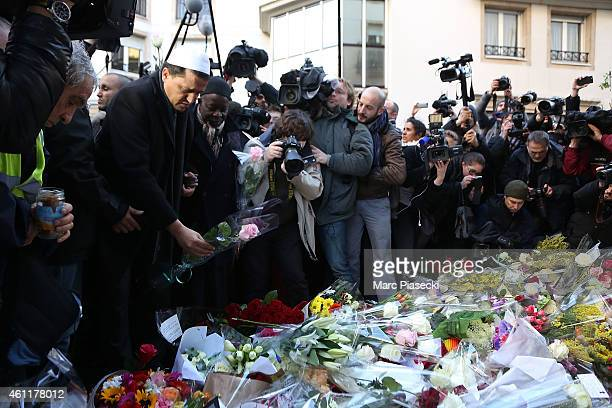 Hassen Chalghoumi Imam of the Drancy mosque in Paris leaves flowers and prays near the 'Charlie Hebdo' offices on a day of mourning following a...