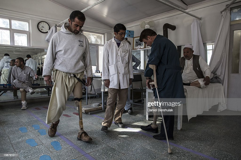 Hassibullah, 30, (L)who lost his after stepping on a mine, practices walking with his new prosthetic leg at the International Committee of the Red Cross (ICRC), orthopedic centreon November 20, 2012 in Kabul, Afghanistan. The ICRC rehabilitation centre works to educate and rehabilitate land-mine victims, and those with limb related deformities, back into society and employment offering micro-credit financing, home schooling and vocational training to patients. The clinic itself is unique in that all of the workers are handicapped. The ICRC centre in Kabul has registered over 57,000 patients and 114,000 countrywide in all of their centres since its inception 25 years ago.
