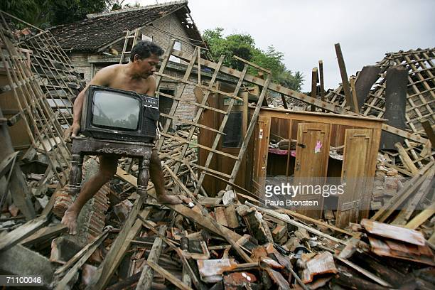 Hassim carries a TV found in the rubble of his destroyed home June 1, 2006 in Bantul, Indonesia. At least 6,200 people were killed when a powerful...