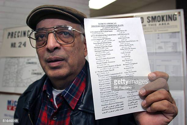 Hasson Ali Muhammed of Dearborn, Michigan holds up a bi-lingual voter guide at Salina School November 2, 2004 in Dearborn, Michigan. Polls are...
