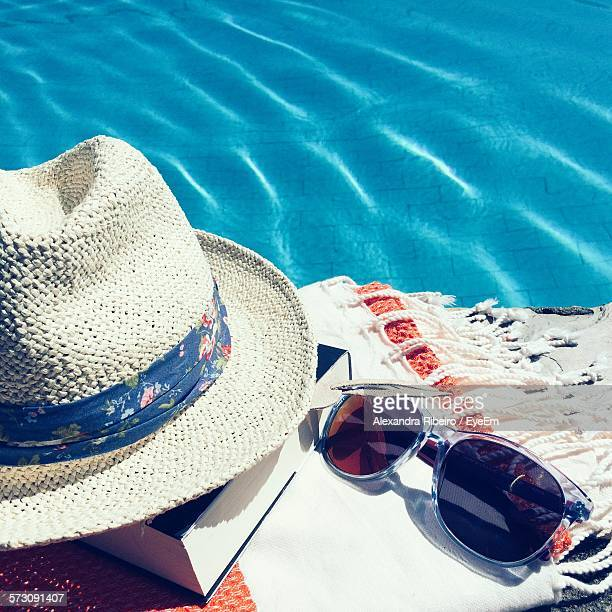 hat and book with sunglasses on scarf by swimming pool - サングラス 無人 ストックフォトと画像