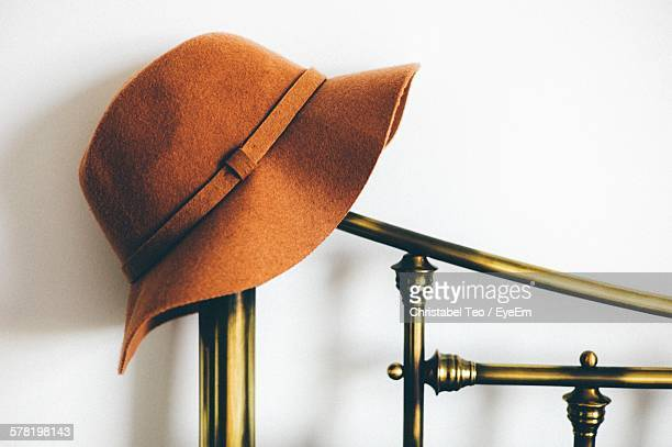 Hat On Stand Against White Wall