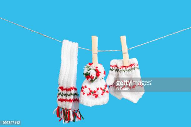 hat, scarf and pair of gloves drying in the open air hanging on clothes line affixed with wooden pegs - froid humour photos et images de collection