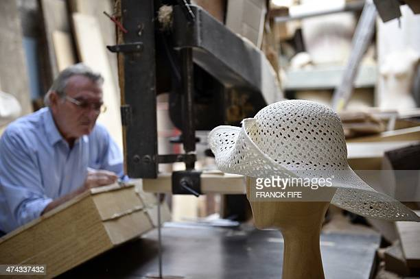A hat sits on a wooden hat block as block shaper Lorenzo Re works in his workshop La Forme in Paris on May 18 2015 Lorenzo Re is one of the last...