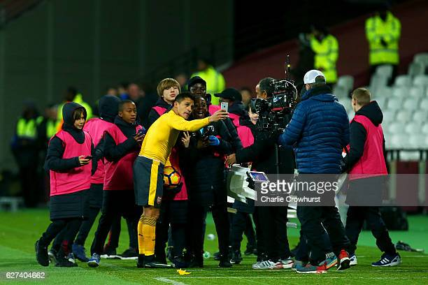 Hat trick hero Alexis Sanchez of Arsenal poses for a selfie photograph with ball kids after the Premier League match between West Ham United and...