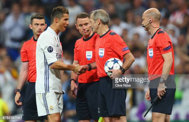 Hat trick scorer Cristiano Ronaldo of Real Madrid shakes hand with referee Martin Atkinson as he collects the match ball after the UEFA Champions...