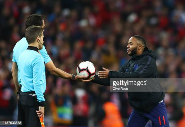 Hat trick scorer Raheem Sterling collects the match ball from referee Artur Dias during the 2020 UEFA European Championships Group A qualifying match...