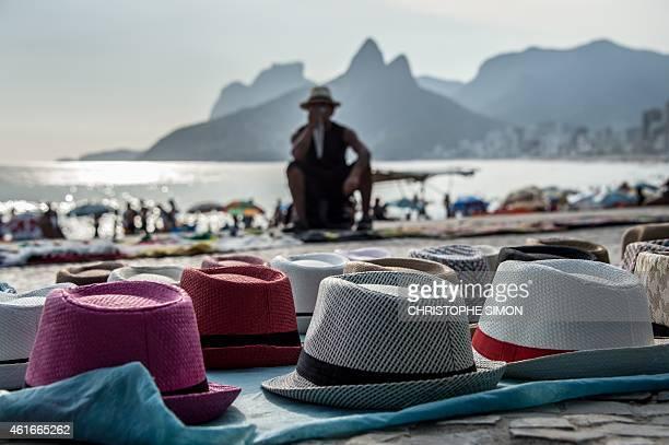 A hat vendor awaits for clients at Arpoador beach in a temperature of 37 degrees Celsius in Rio de Janeiro Brazilon 16 January 2015 AFP PHOTO /...