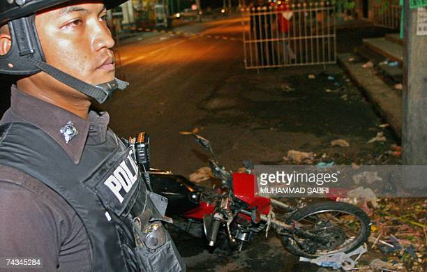 A police officer stands next to a destroyed motorcycle following a bomb blast in Thailand's southern Hat Yai province 28 May 2007 Seven coordinated...