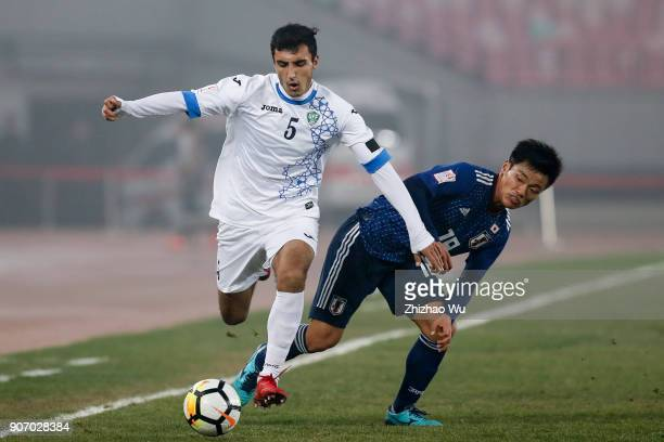Hatate Reo of Japan and Otakhonov Abbosjon of Uzbekistan in action during AFC U23 Championship Quarterfinal between Japan and Uzbekistan at Jiangyin...