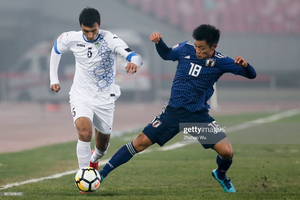 Hatate Reo of Japan and #5 Otakhonov Abbosjon of Uzbekistan in action during AFC U23 Championship Quarter-final between Japan and Uzbekistan at Jiangyin Sports Center on January 19, 2018 in Jiangyin, China.