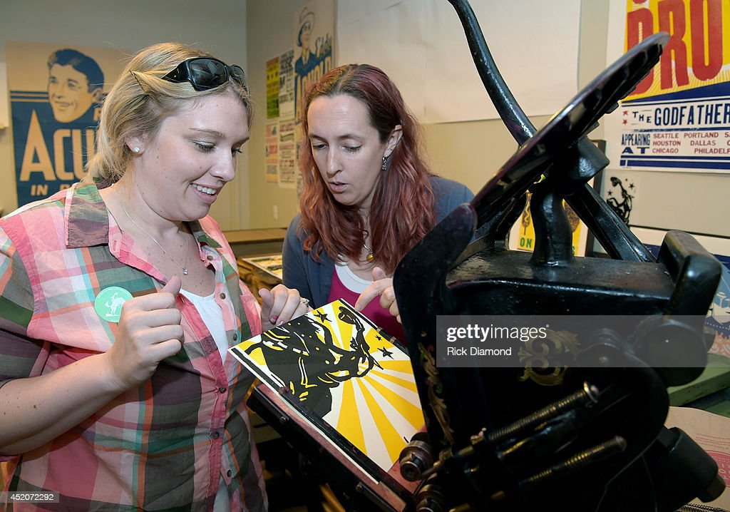 Hatch Show Print tour guide Rebecca Sloan (right) helps attendees print there own Hatch Show Print during the Hatch Show Print tour on July 12, 2014 in Nashville, Tennessee.