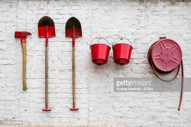 hatchet, shovels, buckets and hose hanging on wall - pelle photos et images de collection
