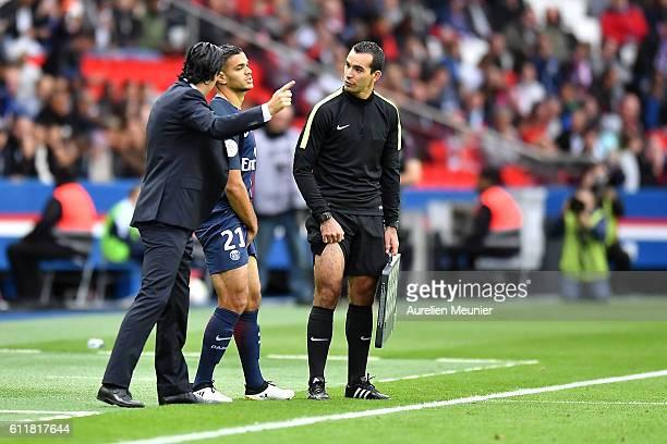 Hatem Ben Arfa of Paris SaintGermain and Paris SaintGermain Head Coach Unai Emery chat before he enters during the Ligue 1 match between Paris...